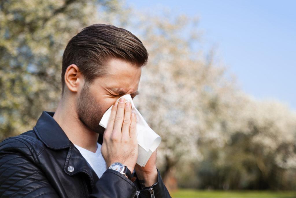 Man sneezing due to allergies