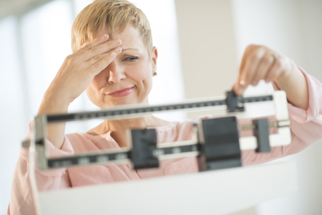 middle aged woman on a scale, dealing with weight gain