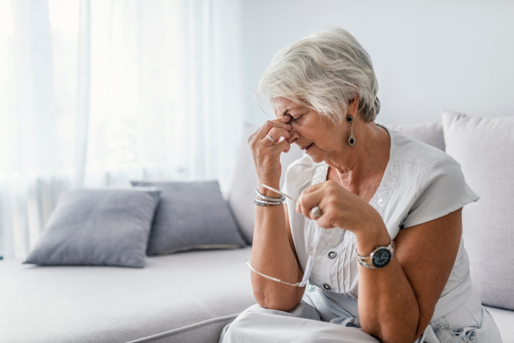 older woman with a migraine (one of the symptoms of poor methylation)