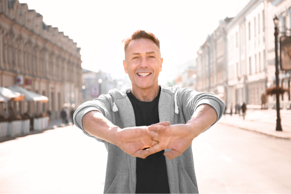 middle aged man with energy, stretching his hands outside