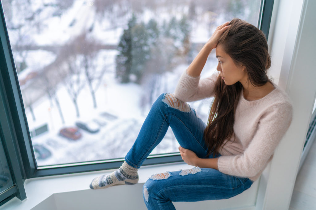 young woman looking out the window at a winter, snowy landscape