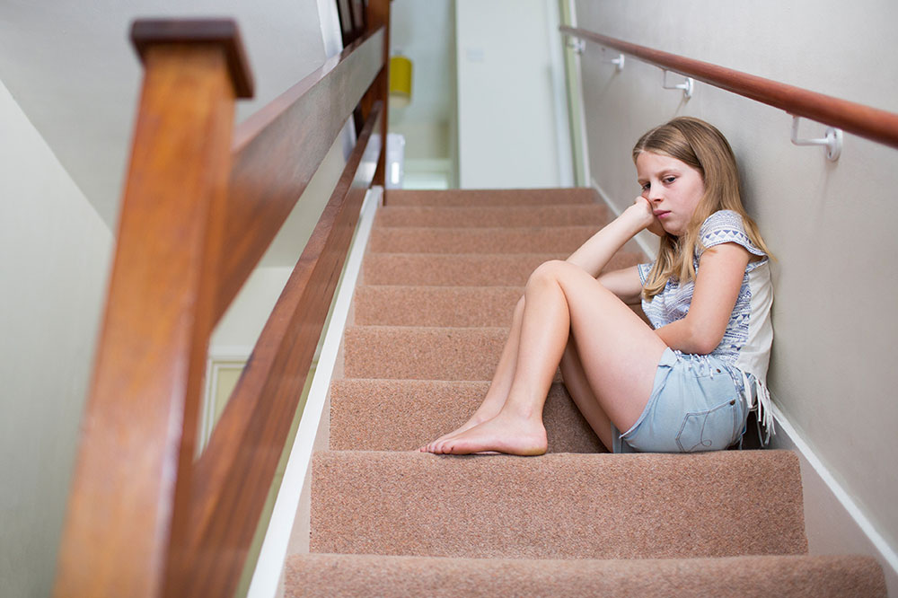 young girl on the stairs upset and anxious