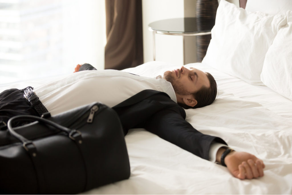 man laying on bed after experiencing jet lag