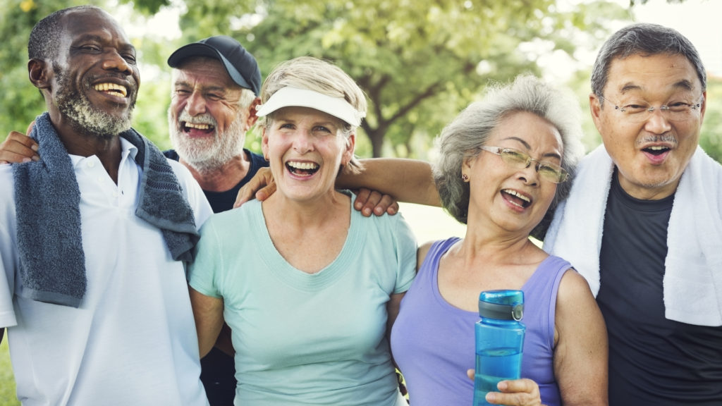 diverse group of healthy old friends outside exercising and happy
