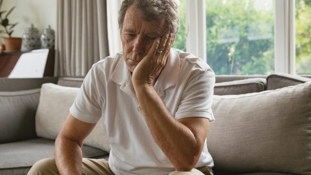 older man sitting on couch looking down and depressed