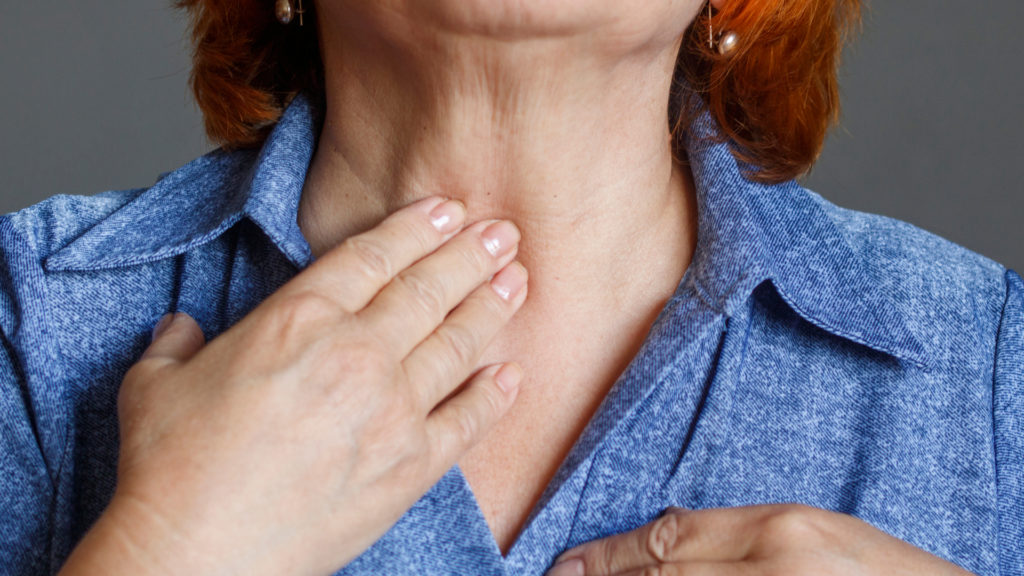 woman feeling throat for hypothyroidism