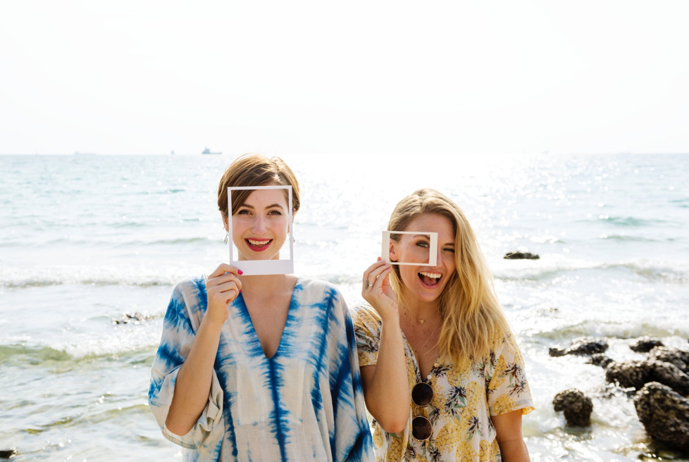 Two women smiling by the ocean