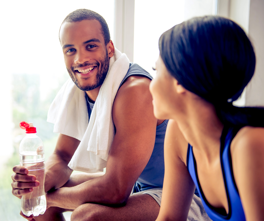 happy couple resting and drinking water after a work out