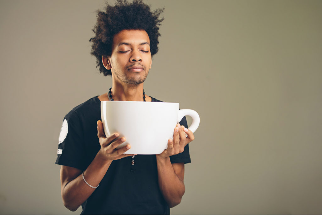 man with a giant cup of coffee