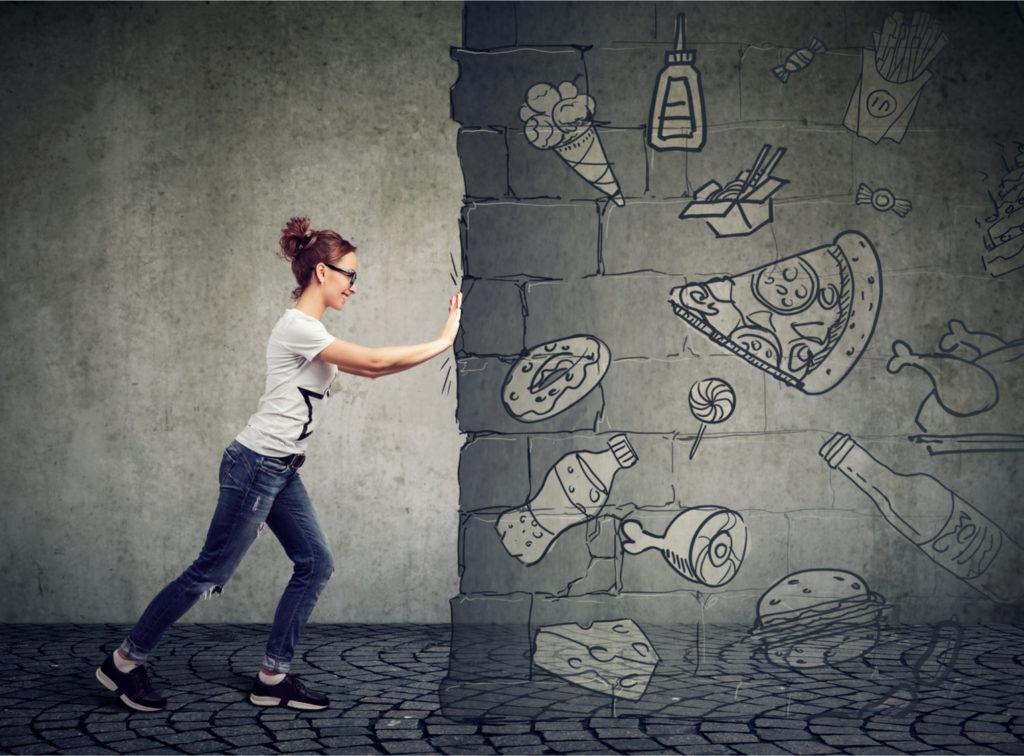 Woman pushing away food cravings