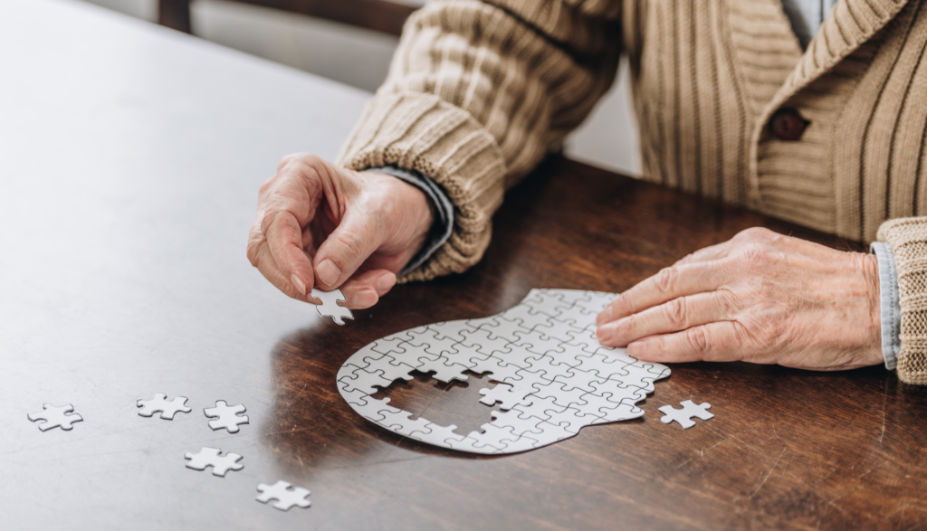 elderly man improving cognitive health by doing a puzzle